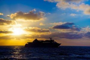 turistfartyg i havet vid solnedgången foto