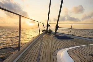 yacht seglar vid solnedgången foto