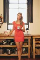 attraktiv ung kvinna i köket med en kopp kaffe foto