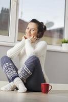 vacker ung kvinna som kopplar av hemma foto
