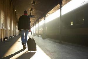 man reser med väska på tågstationen