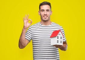 stilig fastighetsmäklare som håller ett hus som gör ok tecken med fingrarna, utmärkt symbol foto