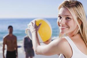 kvinna som leker med bollen på stranden foto