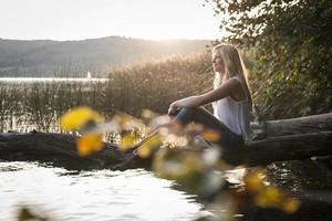 ung kvinna sitter på trädstammen vid sjön foto
