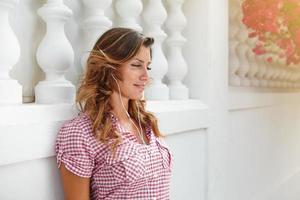ung kvinna ler medan du lyssnar på musik foto