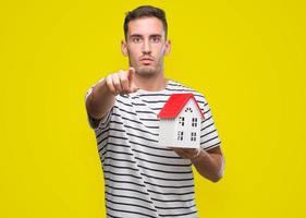 stilig fastighetsmäklare som håller ett hus som pekar med fingret mot kameran och till dig, handtecken, positiv och säker gest framifrån foto