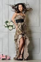 vacker kvinna i lång leopardklänning. foto