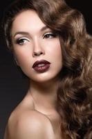 vacker flicka med perfekt hud, mörka läppar och lockar.