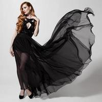 modekvinna i fladdrande svart klänning. vit bakgrund.