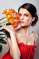 vacker flicka med en orange blomma foto
