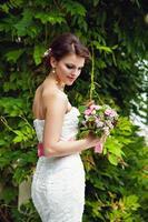 vacker brud med bukett blommor utomhus foto