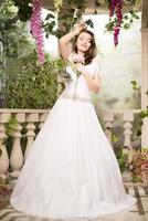 skönhet kvinna i vit klänning. brud, bröllop i trädgården. brunett foto