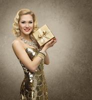 kvinna presentförpackning närvarande, retro vip flicka, lysande guld klänning foto