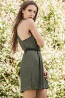 kvinna i trendig grön klänning poserar i sommarträdgård.