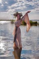 vacker kvinna med blomma krans i watet