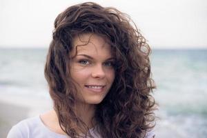 porträtt av en ung söt leende kvinna med brunt hår foto