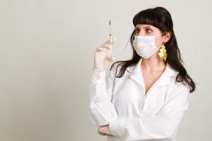 läkare i handskar som visar ampull foto