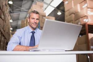 porträtt av lagerchef med bärbar dator foto