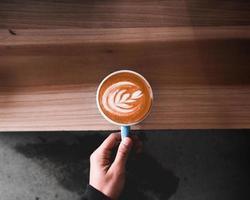person som håller cappuccino latte foto