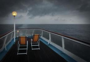två hopfällbara stolar på en båt till sjöss foto