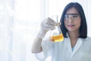 kvinna som håller glasflaskan i labbet foto