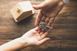 fastighetsmäklare som ger nycklar till kunden foto