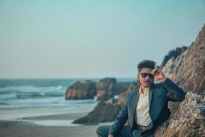 man i kostym på stranden foto