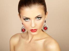 porträtt av vacker brunett kvinna med örhängen. perfekt makeu