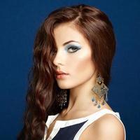 porträtt av vacker brunett kvinna med örhängen. perfekt makeu foto