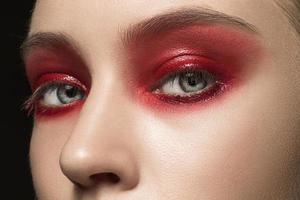vackra unga kvinnliga ansikte med ljusa mode röda smink foto