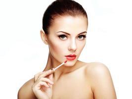 vacker ung kvinna målar läppar med läppstift. perfekt smink