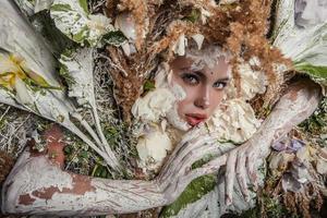 saga flickastående omgiven av naturliga växter och blommor.