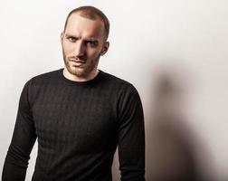 studio porträtt av ung stilig man i casual stickad tröja. foto