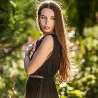 kvinna i lyxig svart klänning poserar i sommarträdgård.