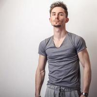 ung stilig man i grå t-shirt. foto
