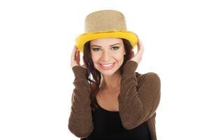 vacker kvinna i svart klänning och gyllene hatt. foto