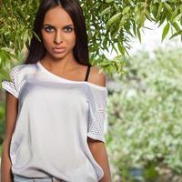 brunett tjej i vit siden skjorta poserar i sommarträdgård.