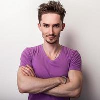 porträtt av en ung stilig man i violett t-shirt. foto