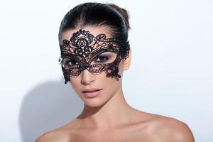 kvinna med smokey makeup på kvällen och svart spetsmask foto