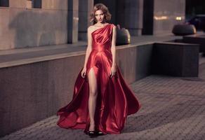 ung vacker kvinna i fladdrande röd klänning. stadsbakgrund.