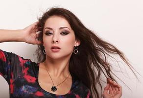 vacker kvinna poserar i halsband och örhängen. närbild