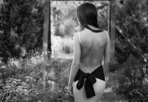 brunett tjej i lyxig klänning poserar i sommarträdgård.