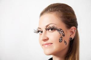 vacker kvinna med långa ögonfransar och ansiktskonst foto