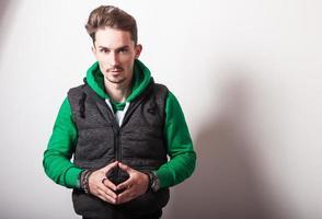 attraktiv ung man i grå väst & grön tröja.