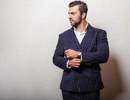 elegant ung stilig man i klassisk mörkblå kostym. foto