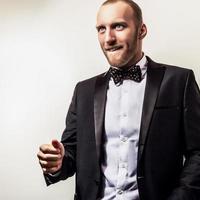 elegant ung stilig man i svart kostym. foto