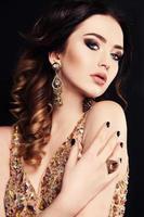 vacker kvinna med mörkt hår och ljus makeup, med bijou foto