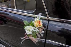 blommor som dekorerar en gammal svart lyxbil foto