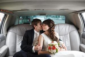 bruden och brudgummen i en bil foto