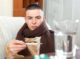 sjuk man som mäter temperatur med termomet foto
